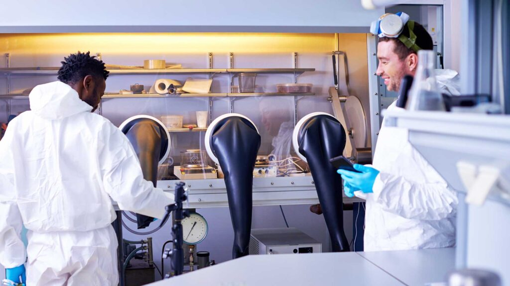 Two scientists working with glove box